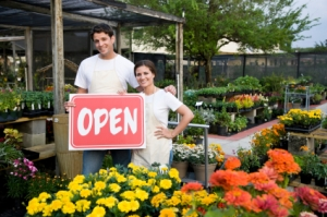 Small business owners holding open sign outside retail plant nursery